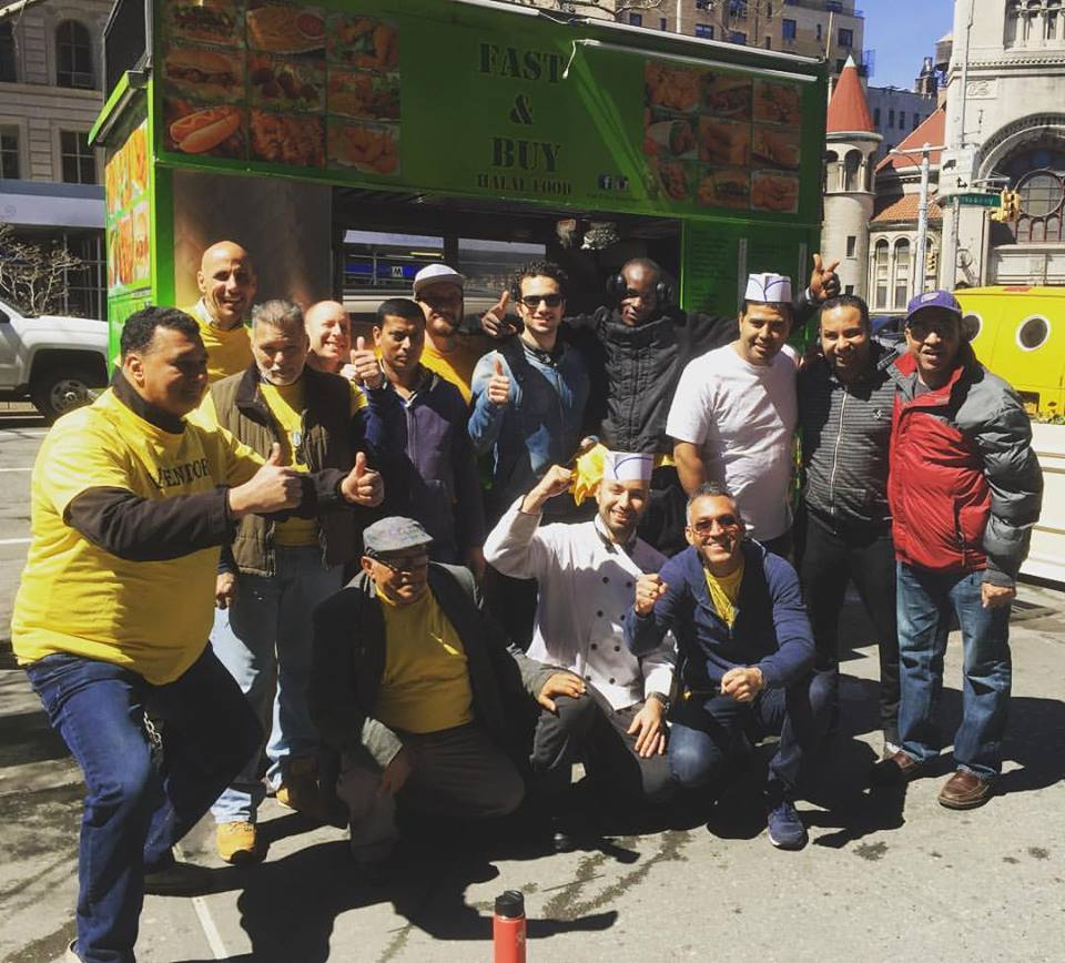 Image of members of our Street Vendor Project giving thumbs up in front of a food cart.
