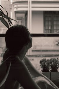 Image of a woman in silhouette looking out a window.