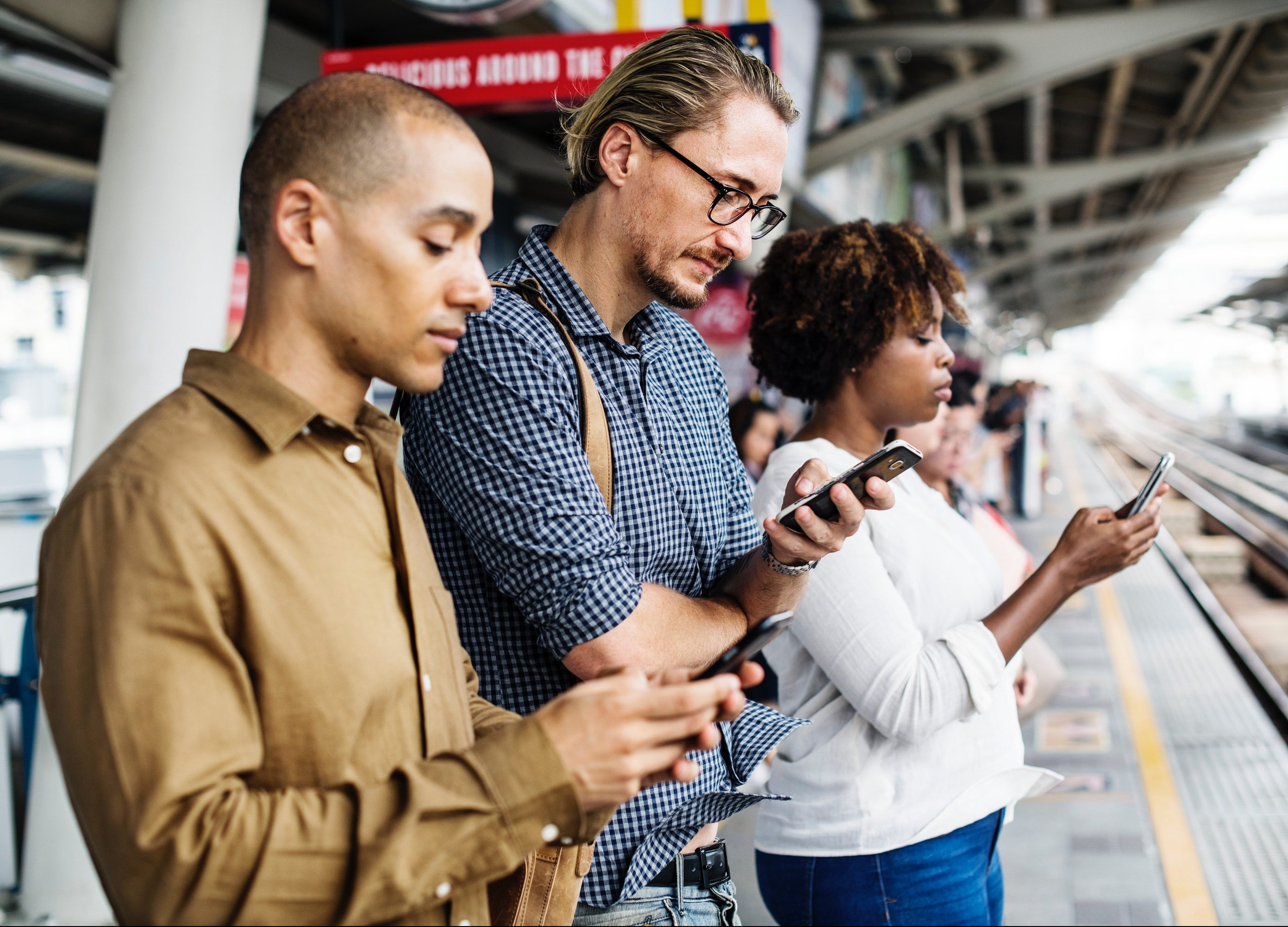 Image of three people looking at their cell phones and waiting for the subway.