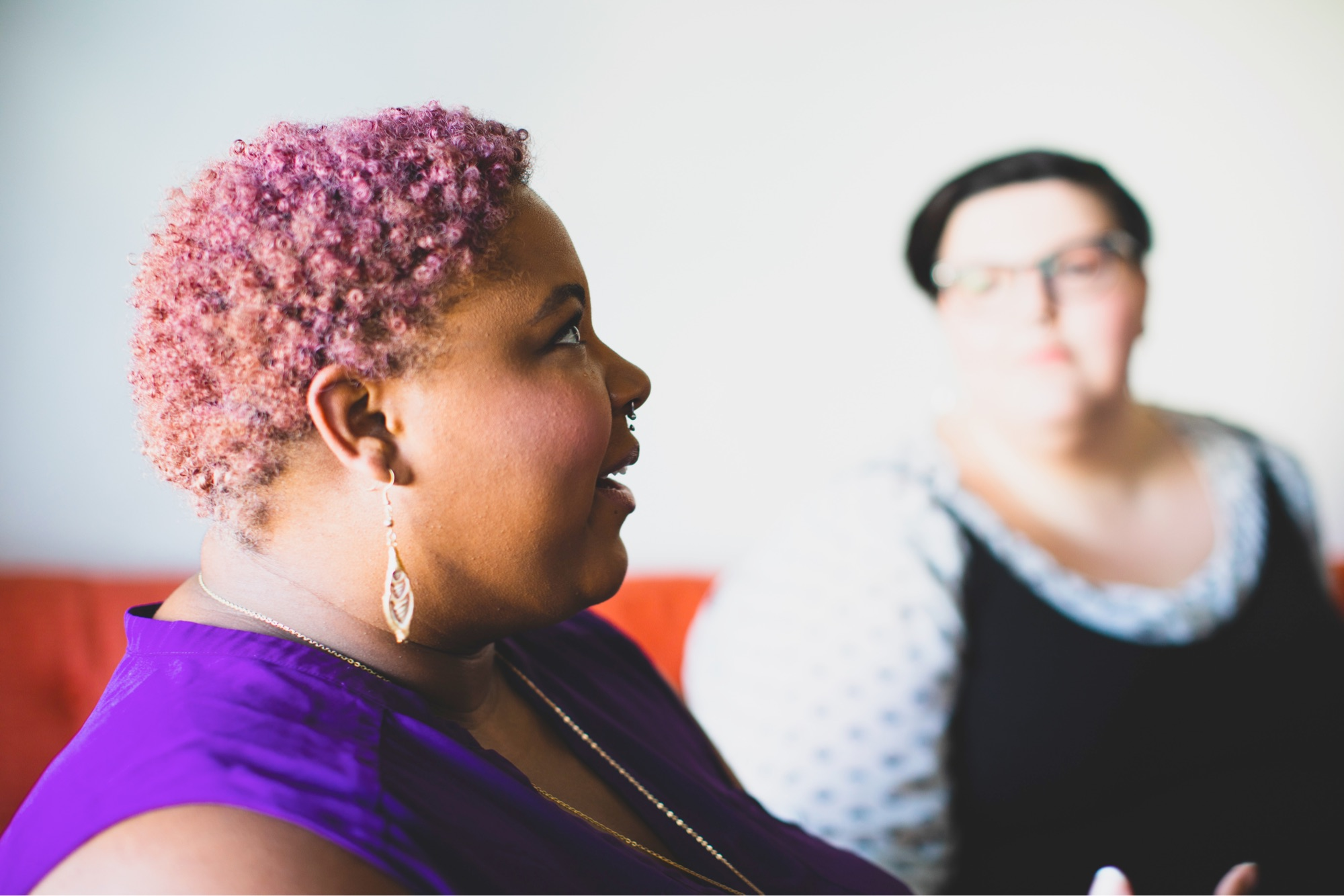 Black femme with short pink hair taking to other person