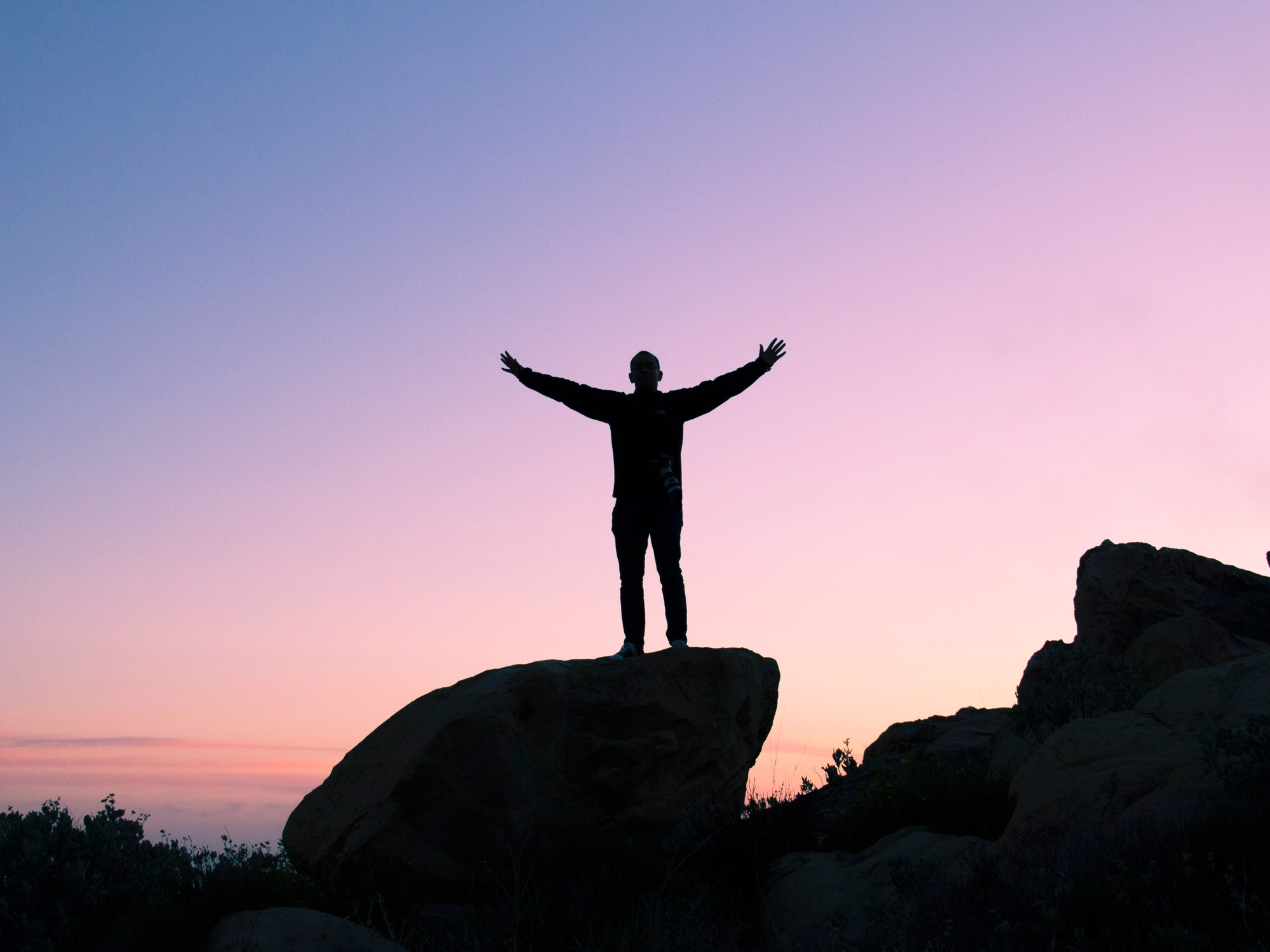 Image of a person standing on a tall rock, at sunrise, with their hands raised triumphantly.